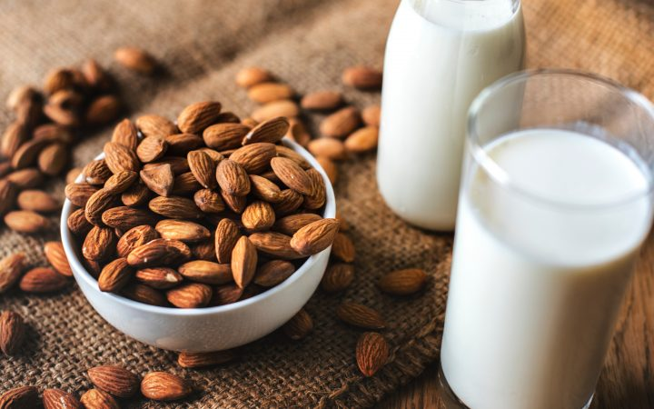 A bottle of almond milk and almonds in a bowl