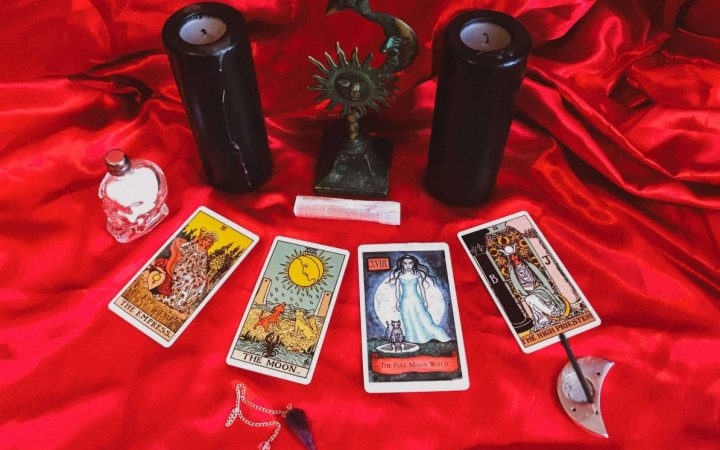 image of tarot cards, two candles and some crystals and a pendulum
