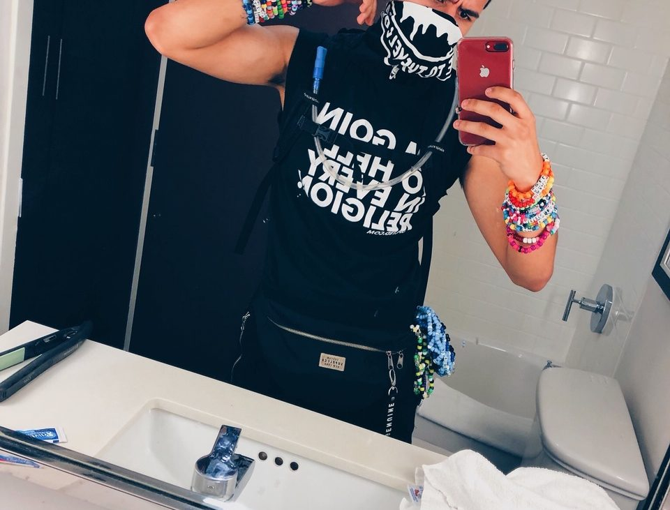 A raver has taken a selfie before attending his rave in his raving attire. He is wearing a bandana, t-shirt and has colourful kandis up his arm.