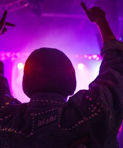 Guy dancing with hands up at a rave event in front of purple lights and DJ
