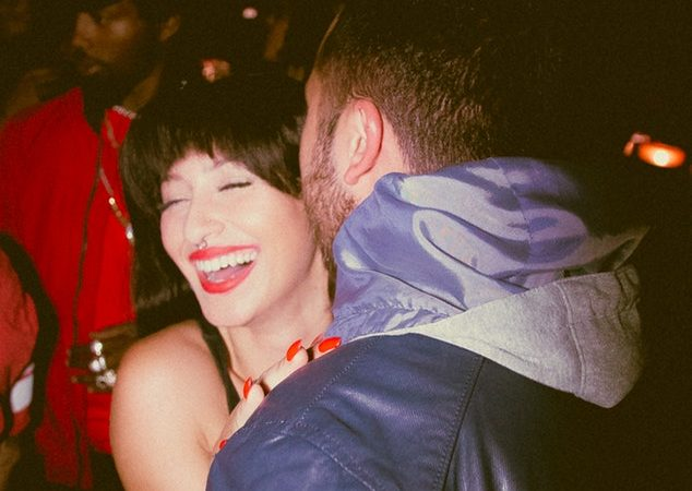 35mm film shot of two people embracing at a rave. Brunette girl with red lipstick on and a guy with his back to the camera talking in her ear
