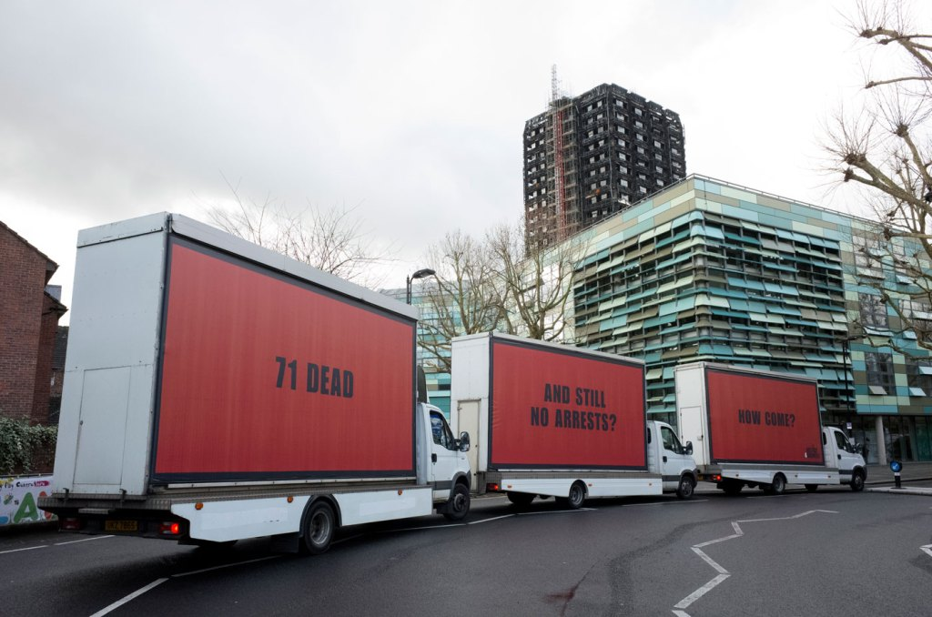 Three billboards demanding accountability parked up outside the Grenfell Tower