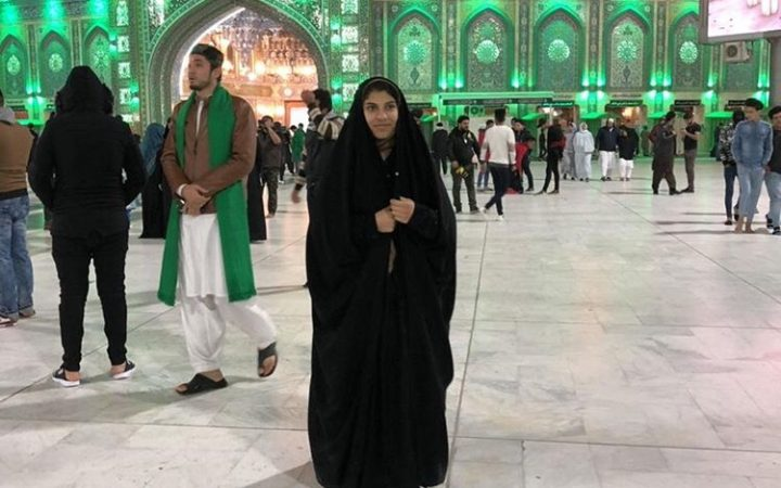 Image depicting girl wearing full religious dress in front of a place of worship.