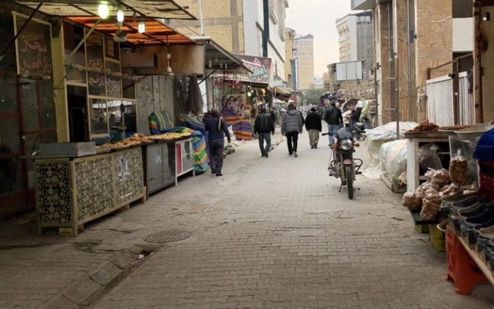 An image depicting a street with stalls and pedestrians.