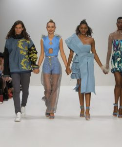 Photograph of London Fashion Week show. Four models walking down the catwalk in FAD clothes.
