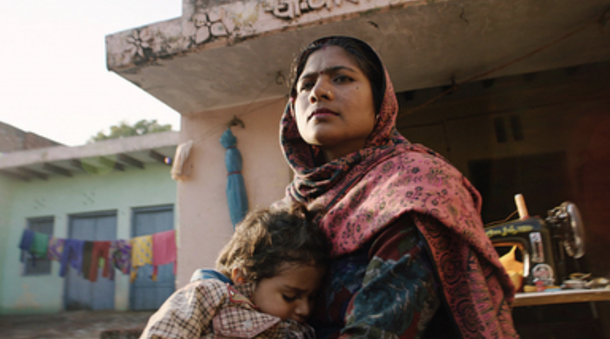 Image of a village woman from a rural village in India and her child hugging her.