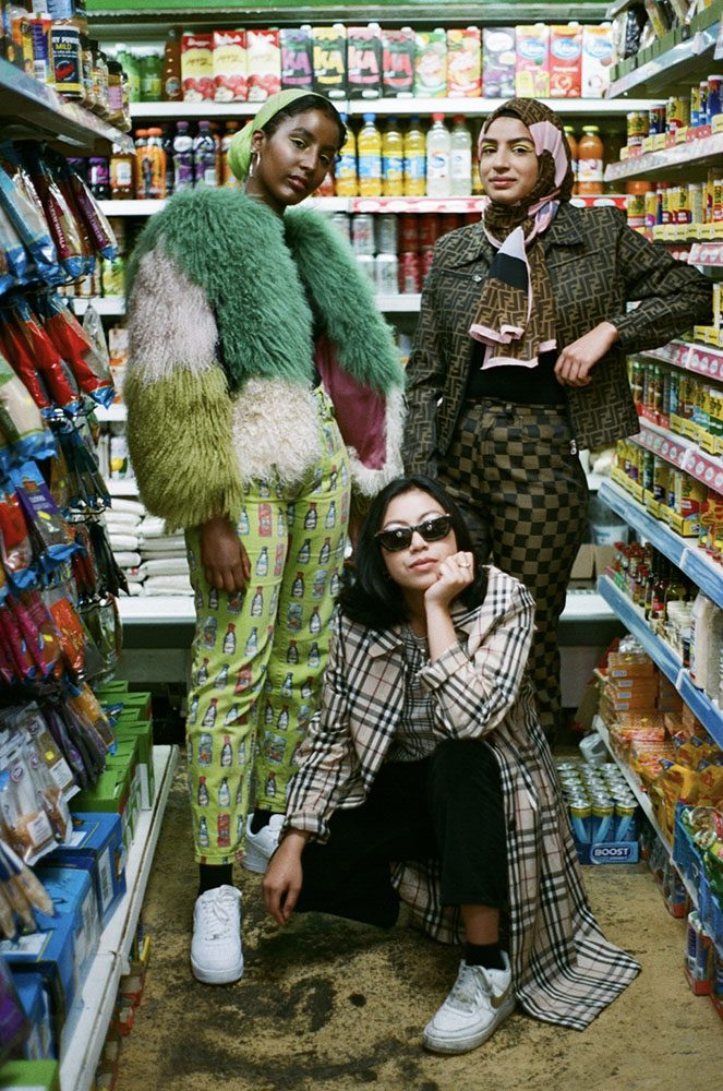 Three young women pose in a cornershop