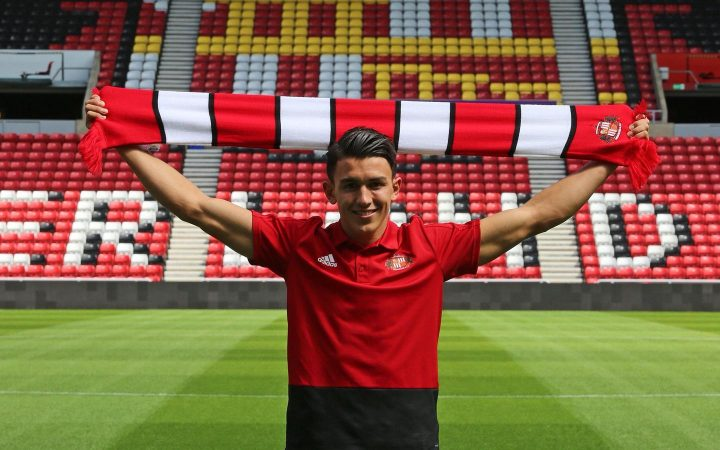 Luke O'Nien professional footballer for Sunderland FC holding up the club scarf in the Stadium of Light