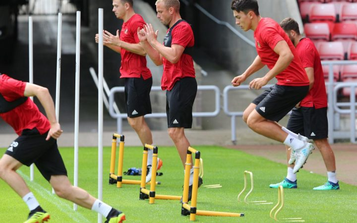 Luke O'Nien professional footballer for Sunderland FC during training. The picture shows him in training uniform jumping over hurdles. The other tam embers are in the background.