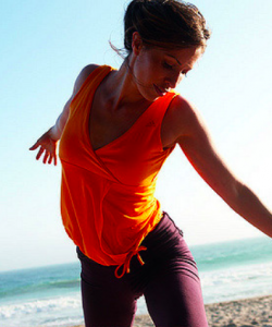 Lady in a bright coloured top stands on the beach. The sea is in the background. She is transitioning from one yoga pose into the next.