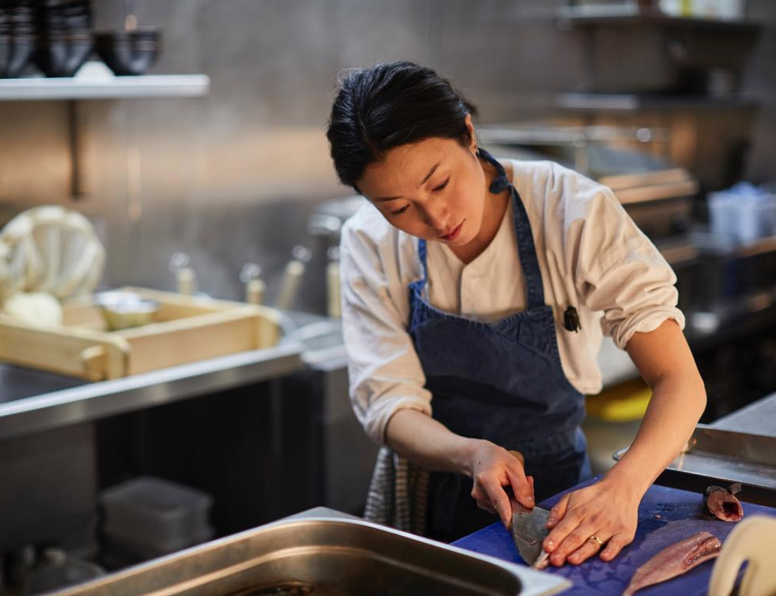 Female Japanese chef cutting a fish in a kitchen