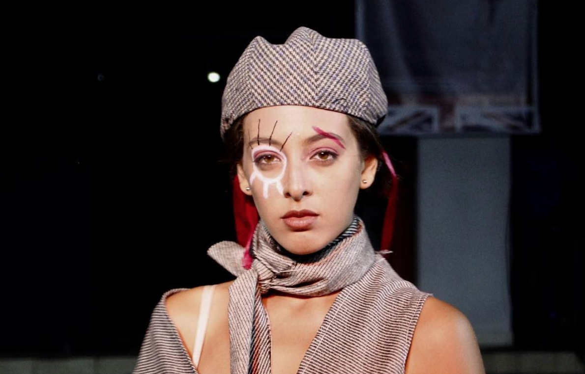 A photo of a model on a runway with heavy eye makeup