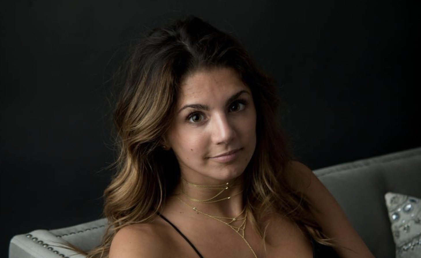 Alexis Mazza sitting on a grey sofa wearing a necklace