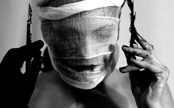 A black and white photo of a woman holding medical tools, with gauze wrapped around her face.