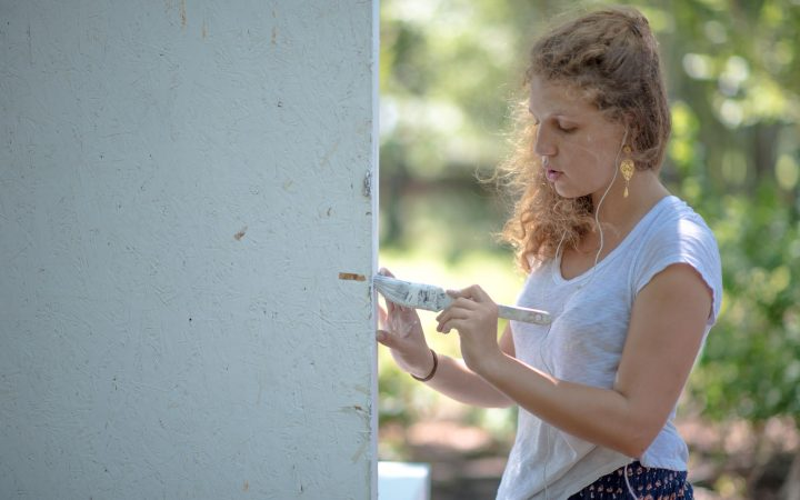 Photo of a girl painting a wall outside