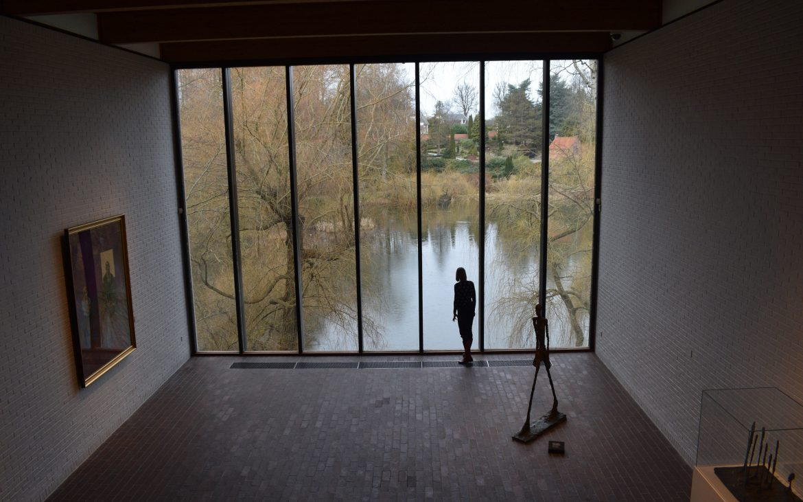 Woman looking out the window next to Giacometti sculpture