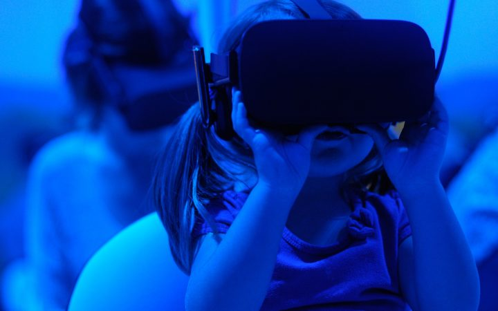 Child using Virtual Reality headset in blue room