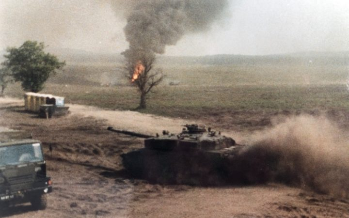 A picture of tanks and a tree set alight in Iraq.