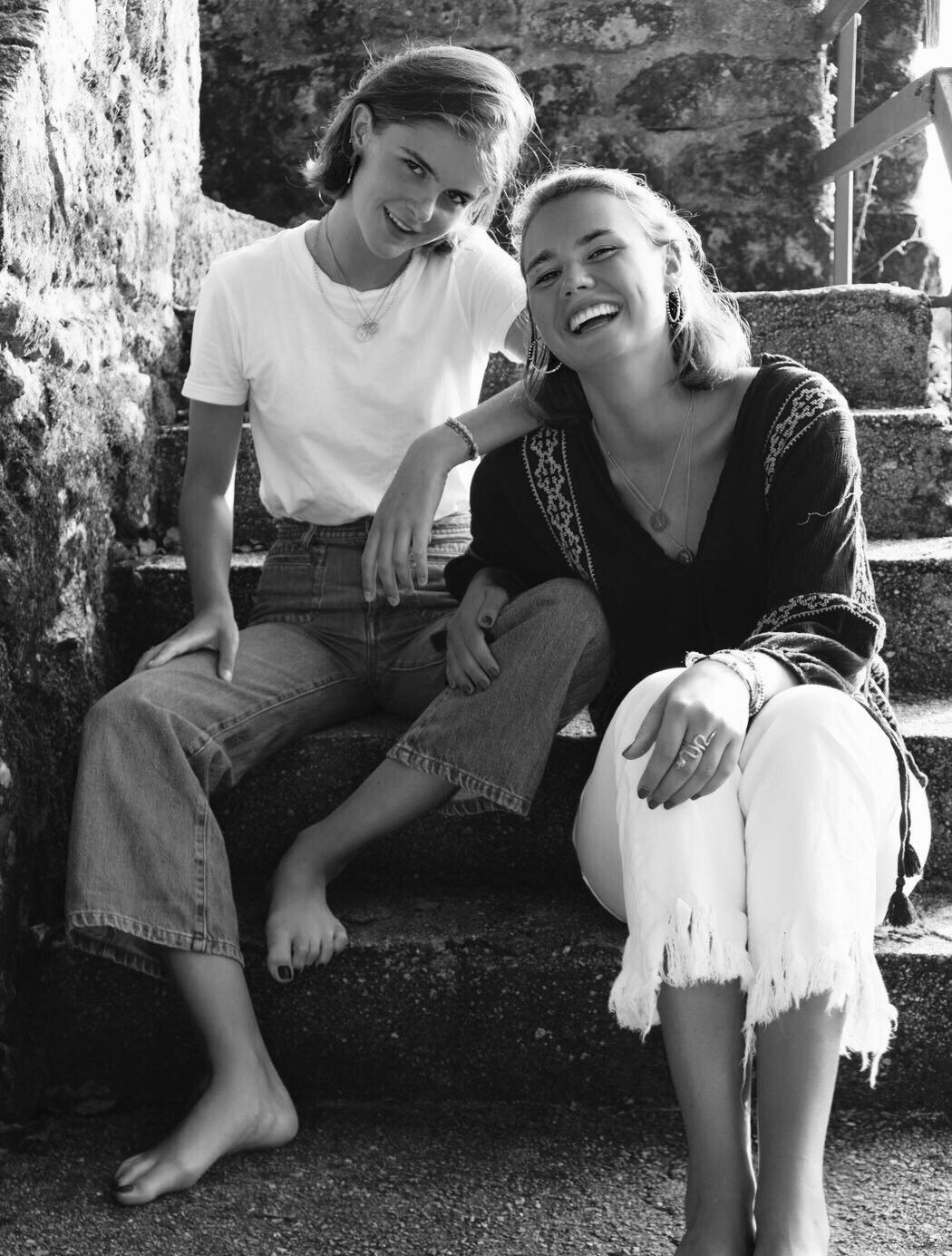 Two girls sit on the steps laughing