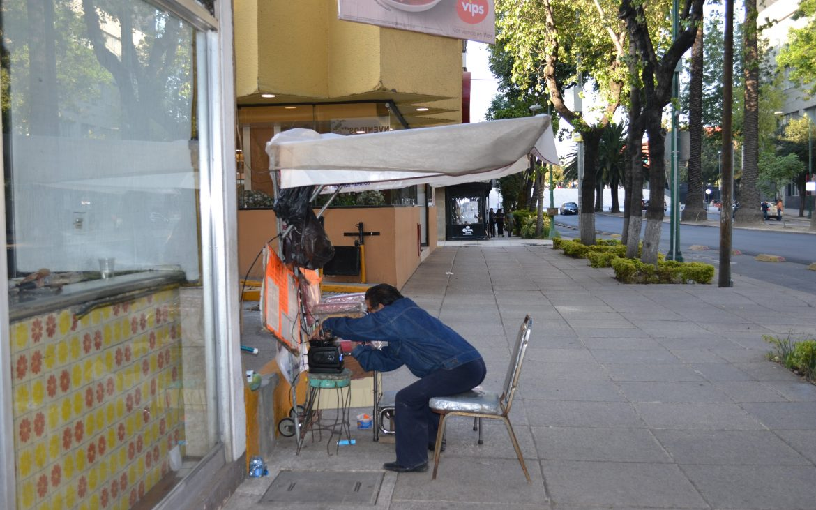 Shoe polisher adjusts his TV as he waits for a customer.