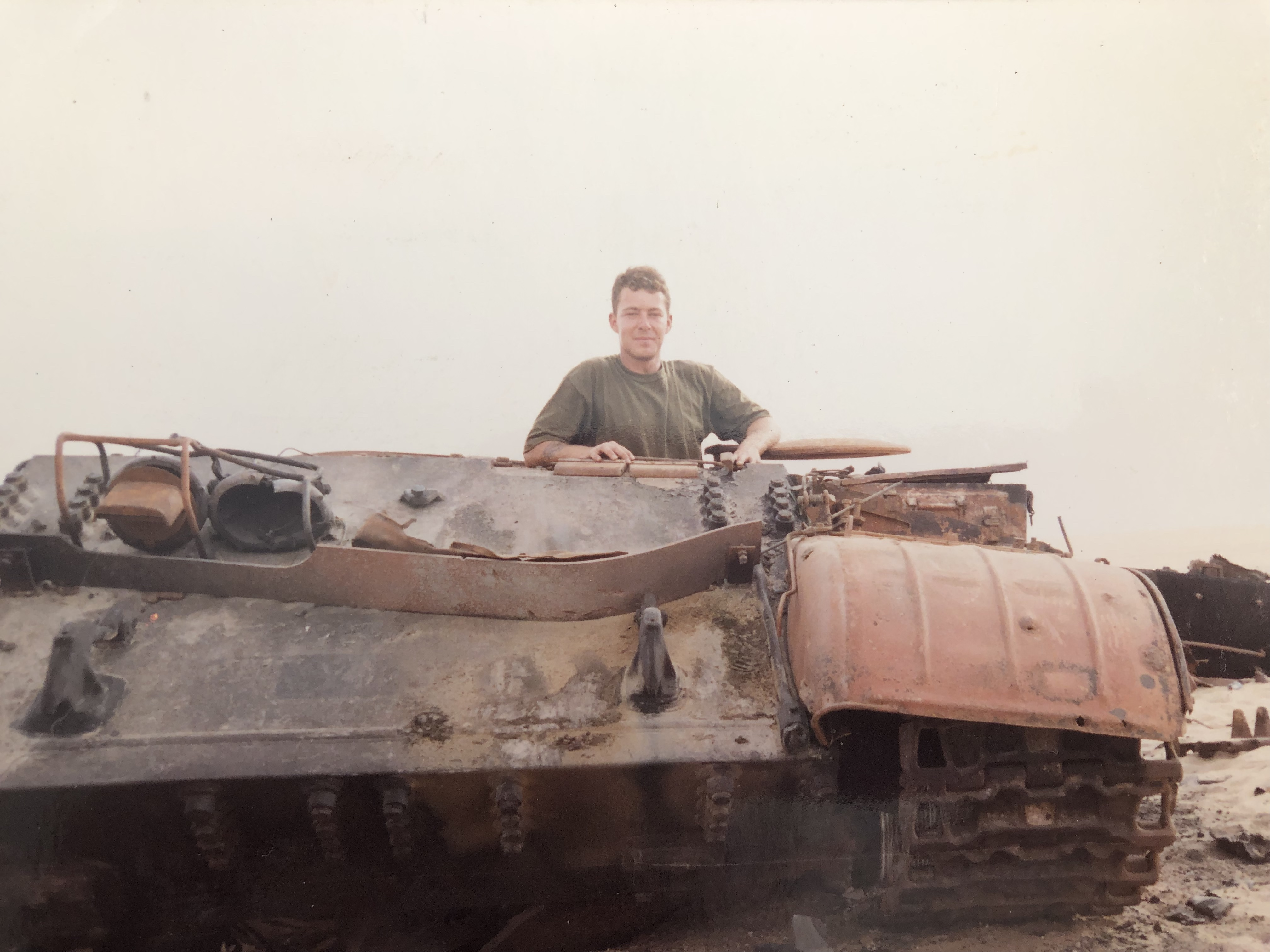 A picture of interviewee John White in a tank in Iraq.