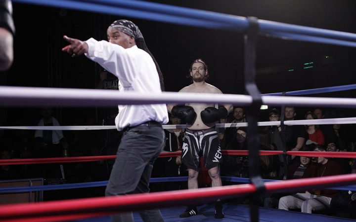 I man stands in the corner of a boxing ring ready to fight. I referee stands in the middle of the ring.
