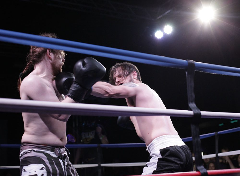 A boxer throws a punch at his opponent