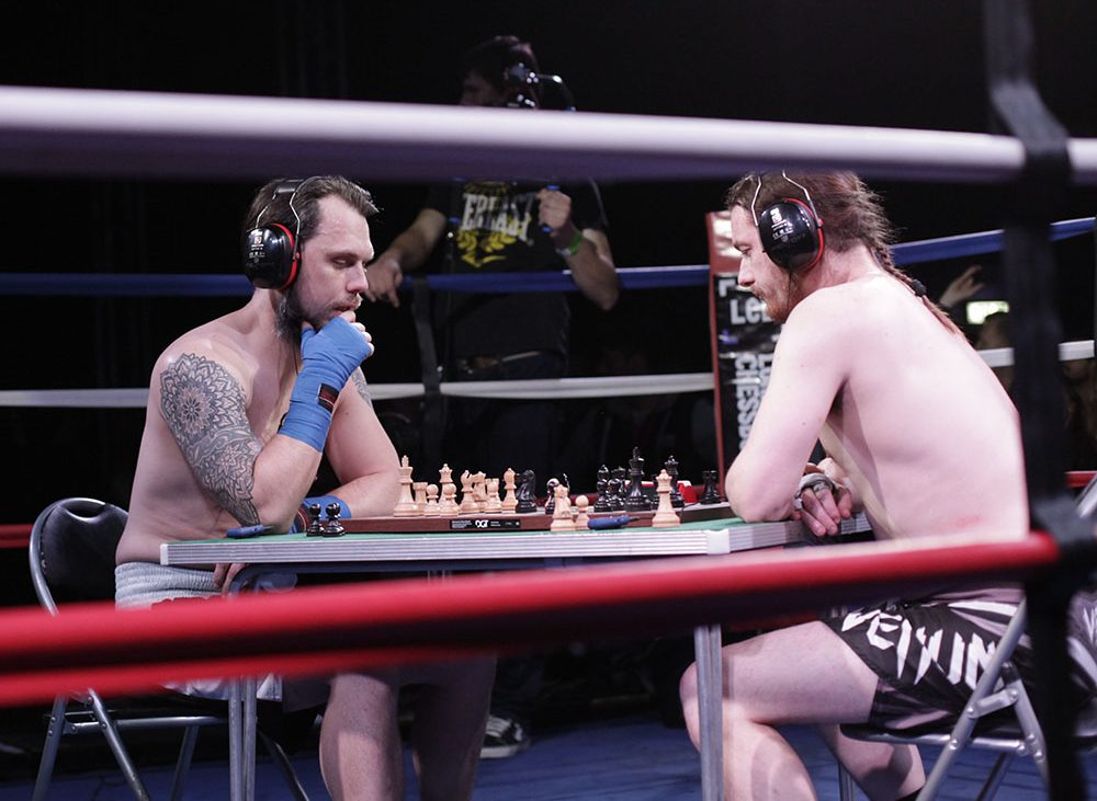 Two men dressed in boxing gear, sit in the middle of a boxing ring and play a game of chess.
