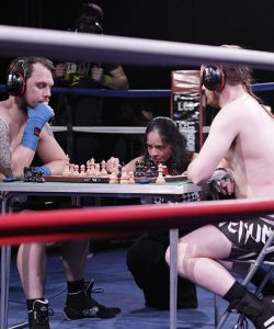 Two men in sports gear sit at a table and play a game of chess. They are sitting in the middle of a boxing ring. They are competing in the sport of 'chessboxing'