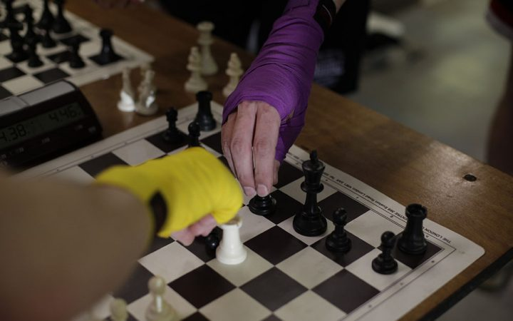 Two hands wrapped in boxing hand wraps, both reach for chess pieces over a chess board.