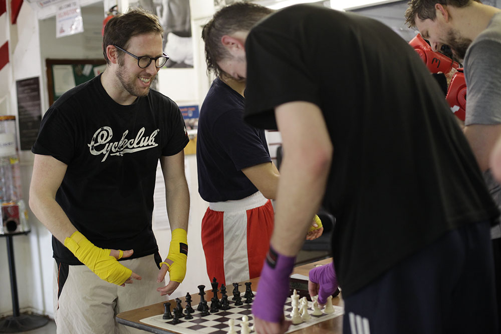 Chessboxing training. Three men gather around a table to play a round of chess. They are wearing sports clothes and boxing hand wraps.