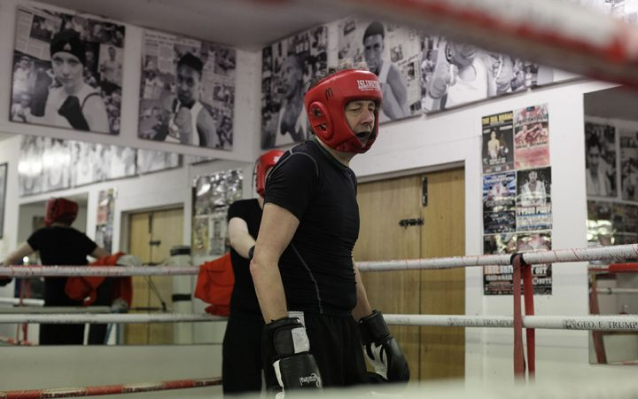 A man wearing protective boxing gear, stands in the middle of a boxing ring after a round of sparring.