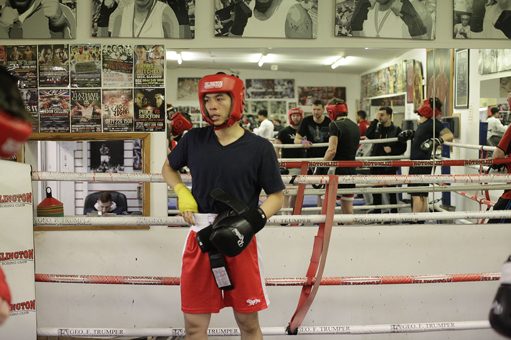 A man stands in a boxing ring. He is wearing protective headgear and boxing gloves. He is getting ready for a round of sparring.