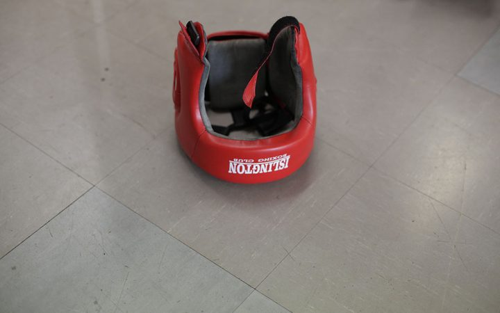 A boxing headguard lies on the floor, after a fighter discarded it after a sparring session.