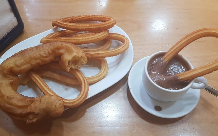 A plate of Churros and Porras with a cup of Hot Chocolate