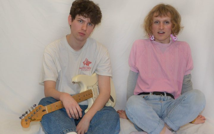 Two musicians pictured together in front of a white screen, holding a guitar.