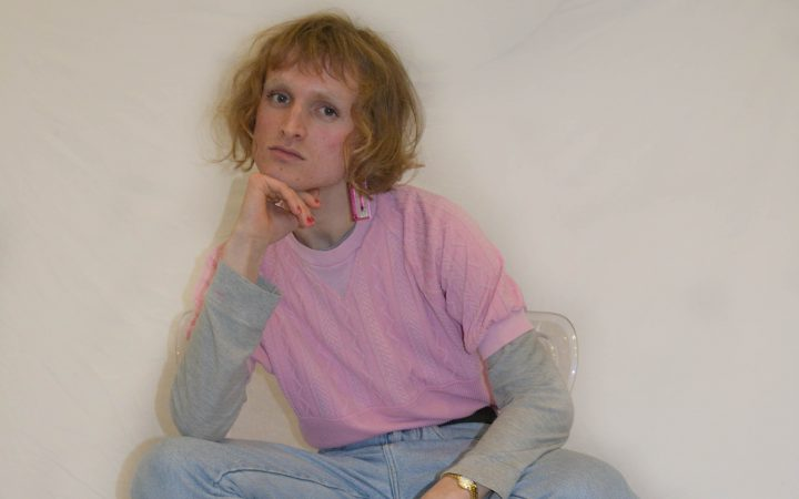 A man dressed in pink, kneeling on a chair.