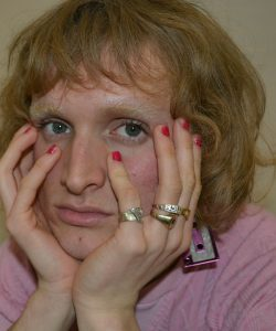 Person holding head in jewellery covered hands, looking at camera