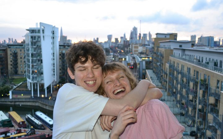 Two boys hugging in front of the London skyline.