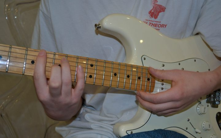 Hands strumming the strings of an electric guitar.