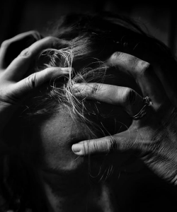Black and white photograph of woman holding her head with her hands