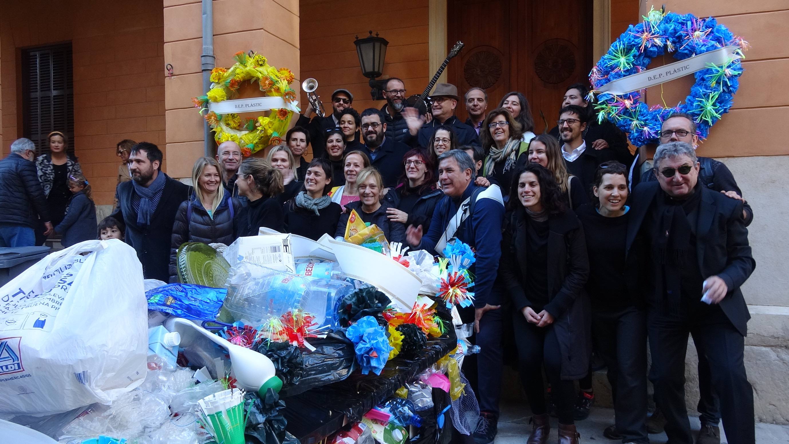 spanish people surrounding the the car with lots of flowers and plastic waste on it