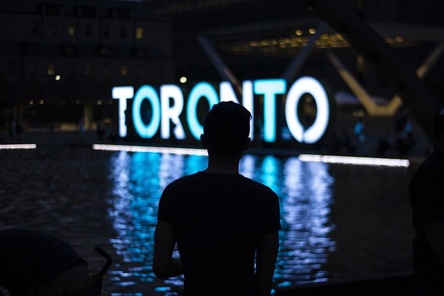 man infront of neon sign spelling out toronto