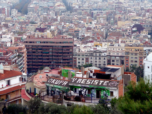 view of barcelona with building in view saying 'occupy and resist'