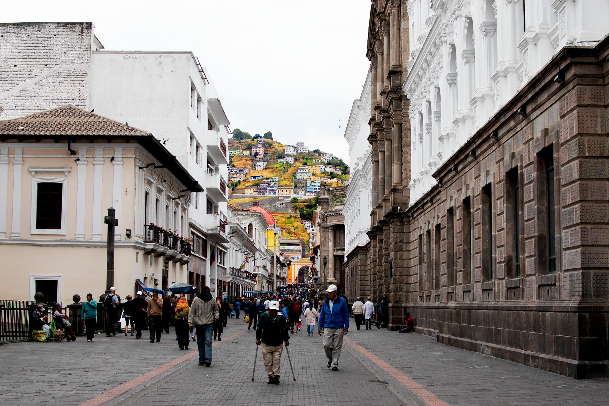The town of quito with colourful yellow houses on the hill in the background