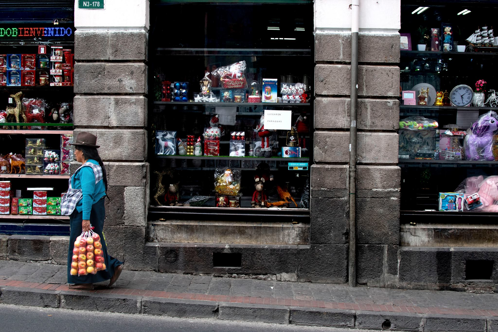 a shop window in quito with woman walking past