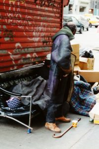 passerbys look at homeless man and his sleeping set up