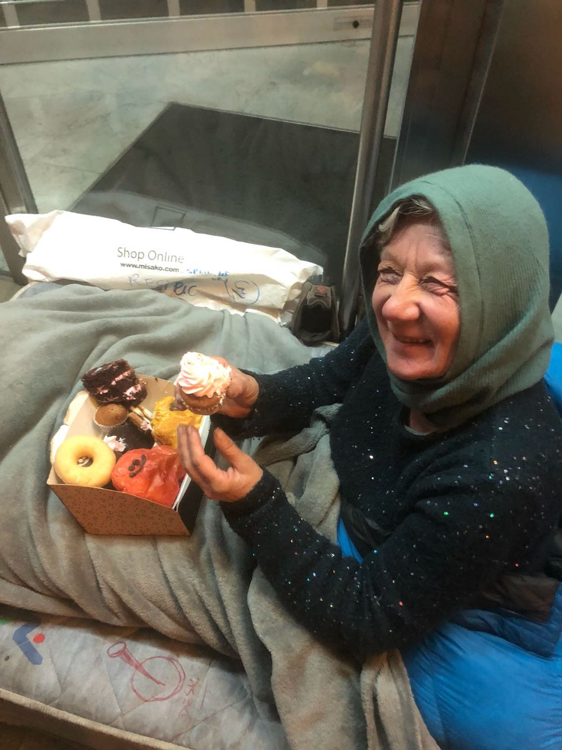 homeless woman smiling selling cakes