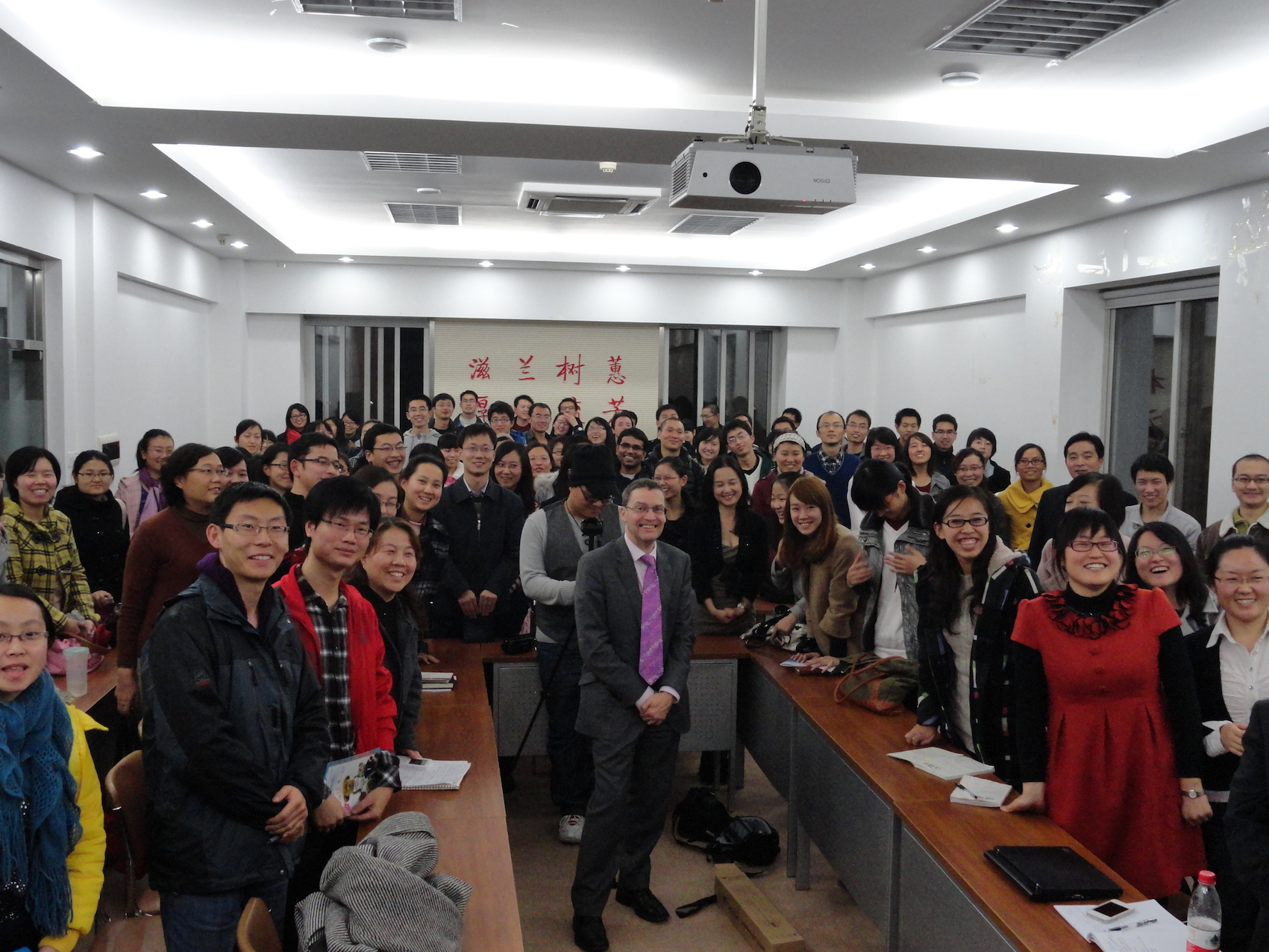 chinese students and their teacher pose for a picture in their classroom