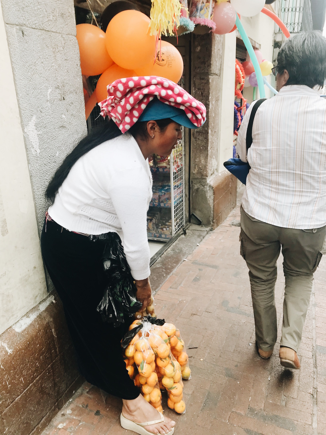 woman carrying a bag of oranges in the street